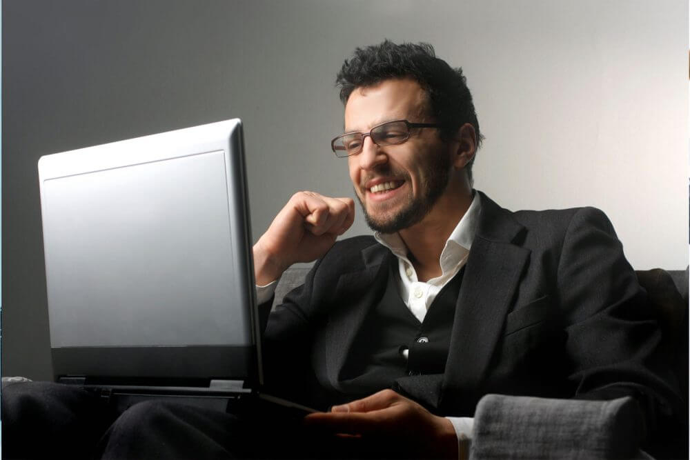 a man smiling in front of a laptop