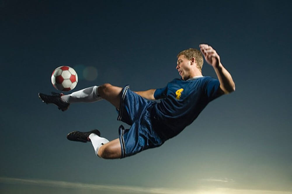 A footballer kicking the ball