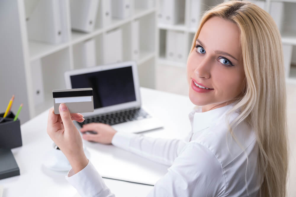 Businesswoman sitting at desk in office and holding credit card