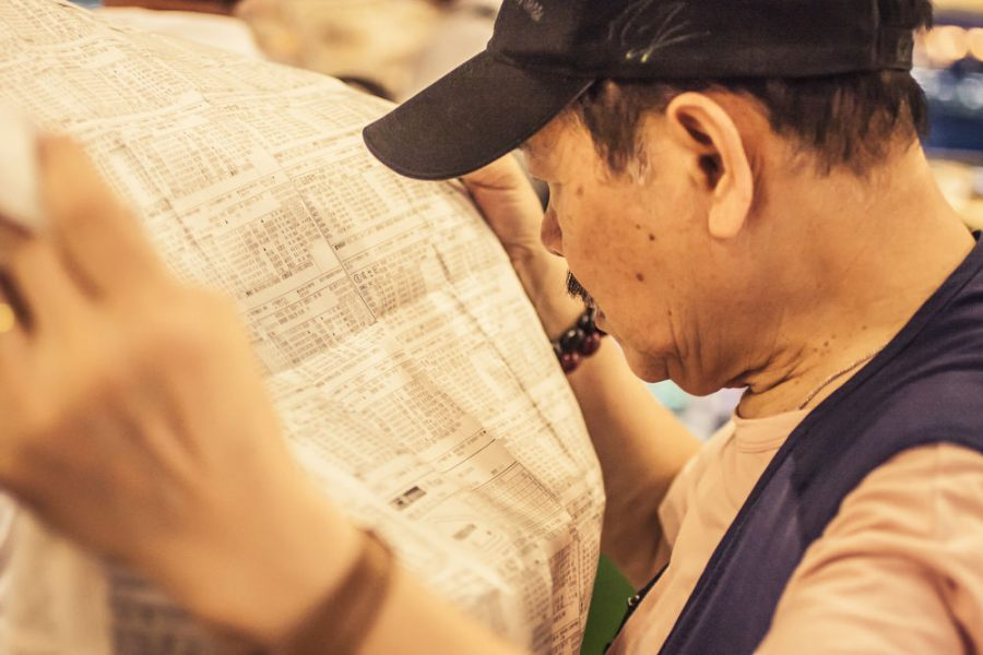 Man reading a newspaper to make bets on horse races