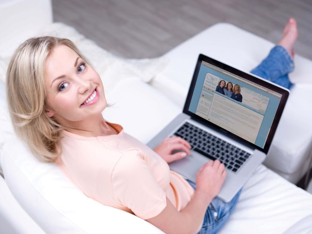A woman with a laptop smilling
