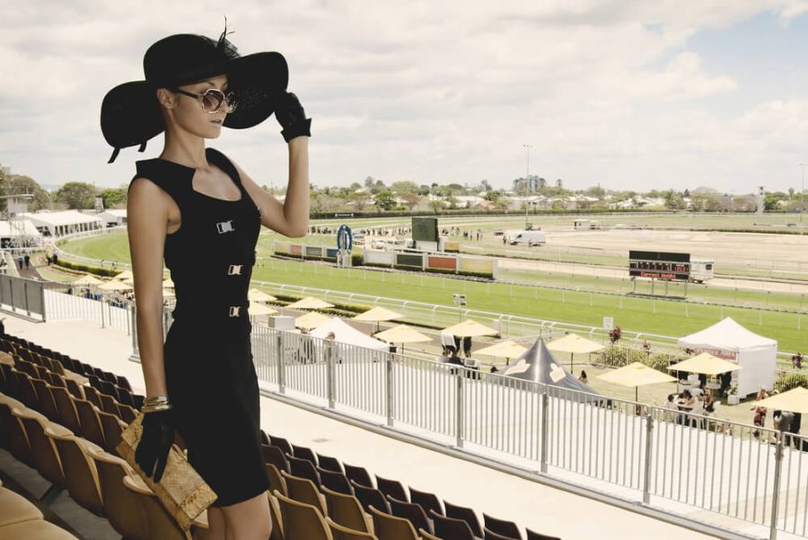 beautiful lady in a proper outfit for horse racing day