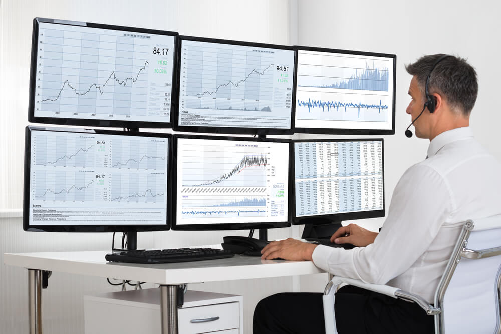 broker looking at graphs on multiple screens