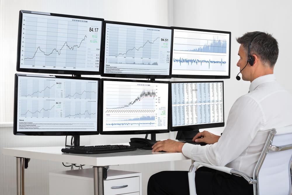 broker looking at graphs on multiple screens