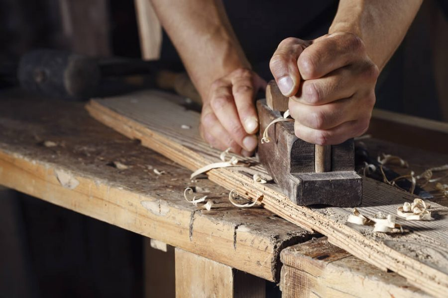 carpenter planing a plank