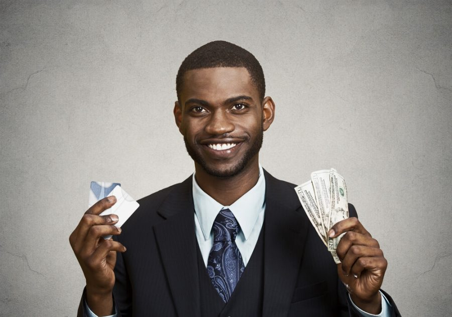 employee standing, holding dollar bills, credit card