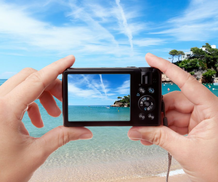 holding digital photo camera on vacations
