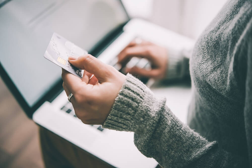 holding plastic credit card and using laptop