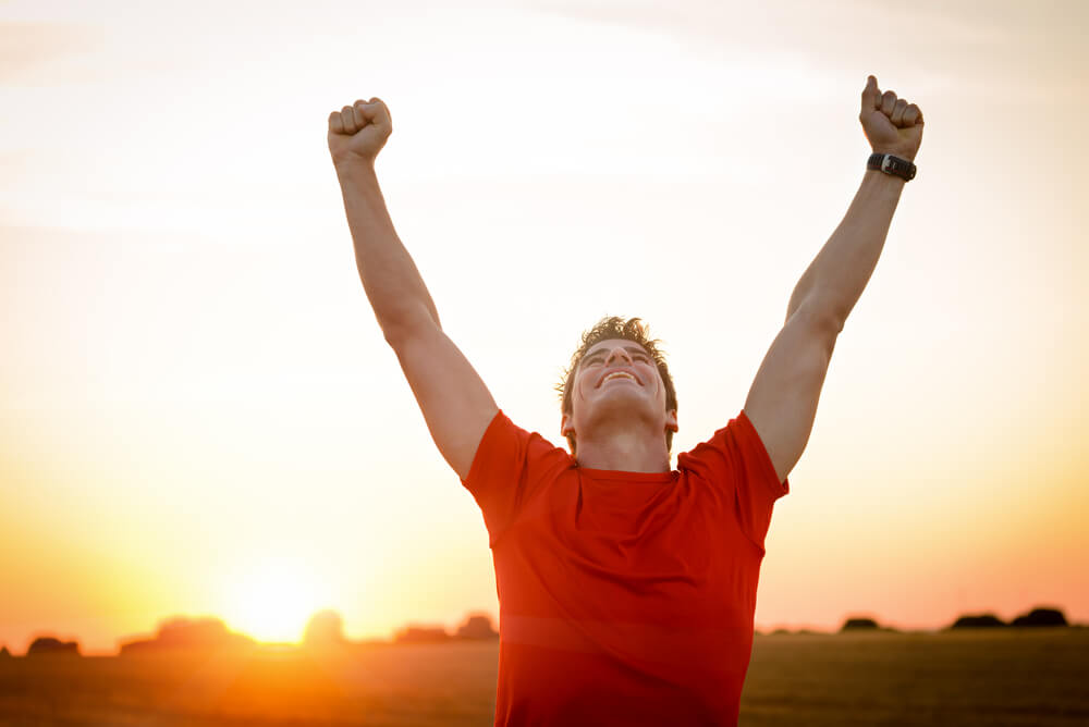 man with arms up celebrating success and goals