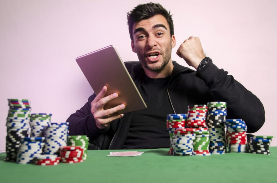 man with tablet playing online poker