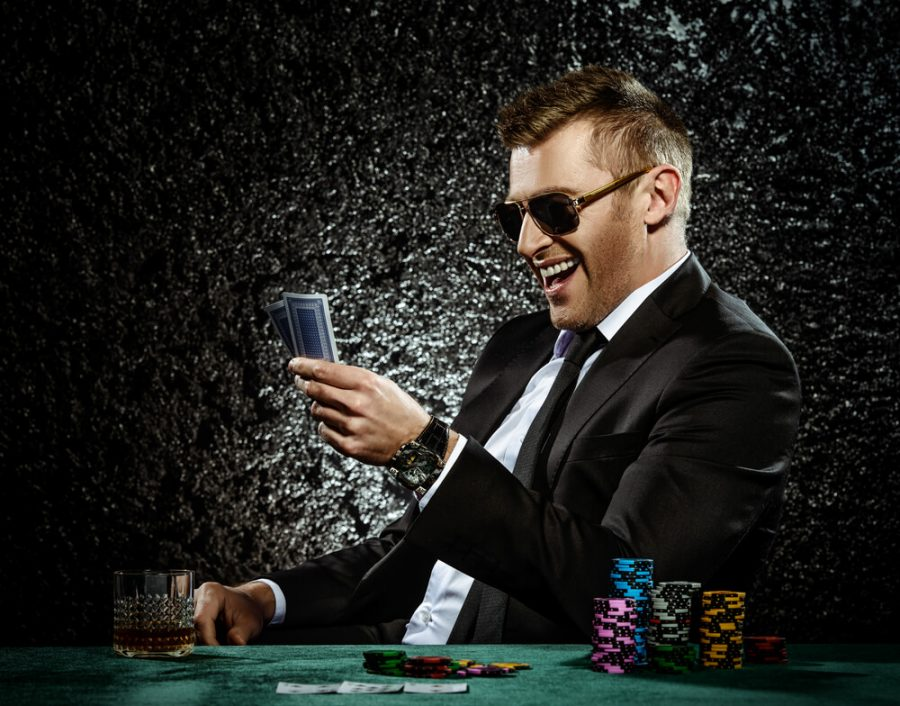 mature man drinking brandy and playing poker