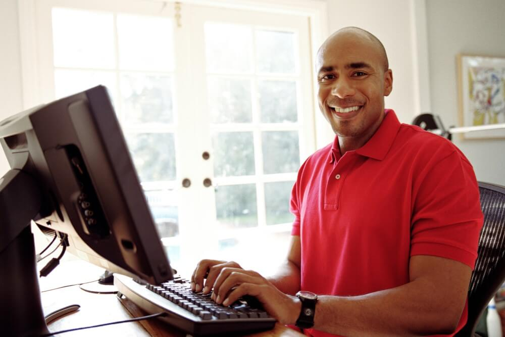A man with a desktop smiling