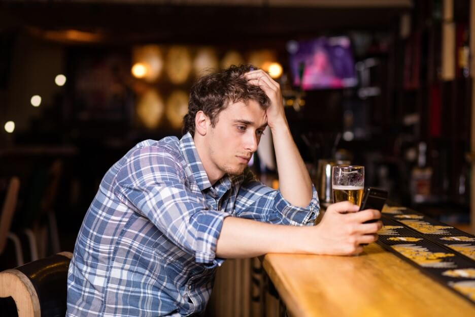 sad single man drinking beer