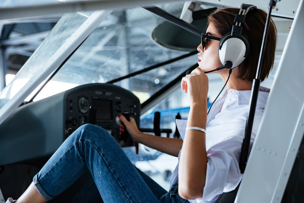 woman pilot sitting and talking with headset
