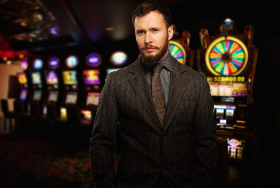 well-dressed man against slot machines